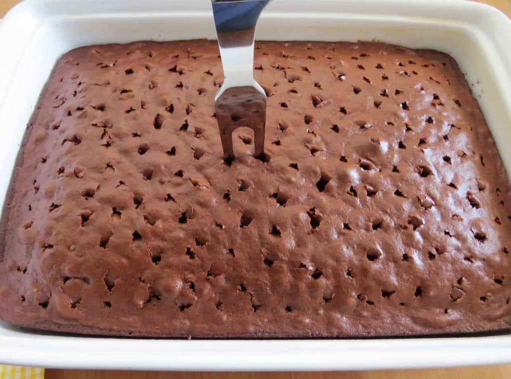 a large meat fork piercing holes in fully baked chocolate cake in a white baking dish