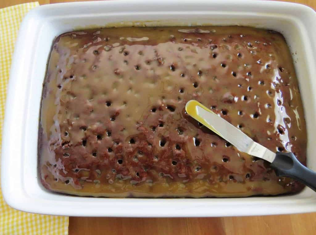an offset spatula spreading out caramel sauce on chocolate cake