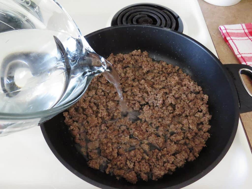adding water to ground beef mixture