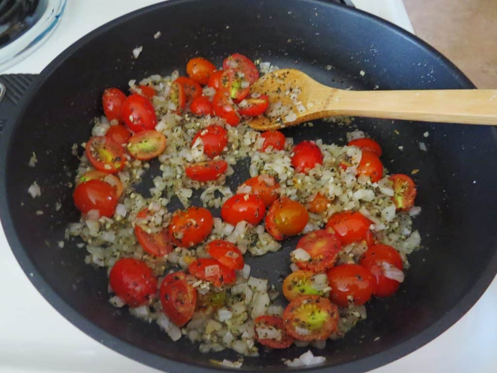 sliced grape tomatoes and Italian seasonings added to skillet with sautéed onions