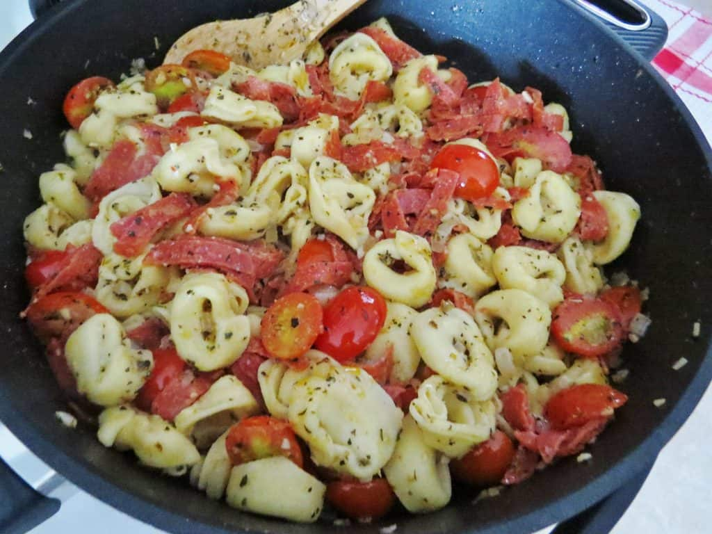 sliced pepperoni and cooked cheese tortellini added to skillet