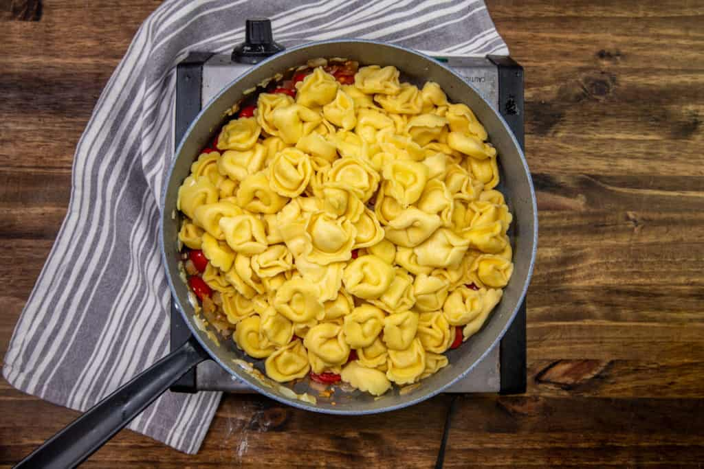 cooked cheese tortellini added to large skillet