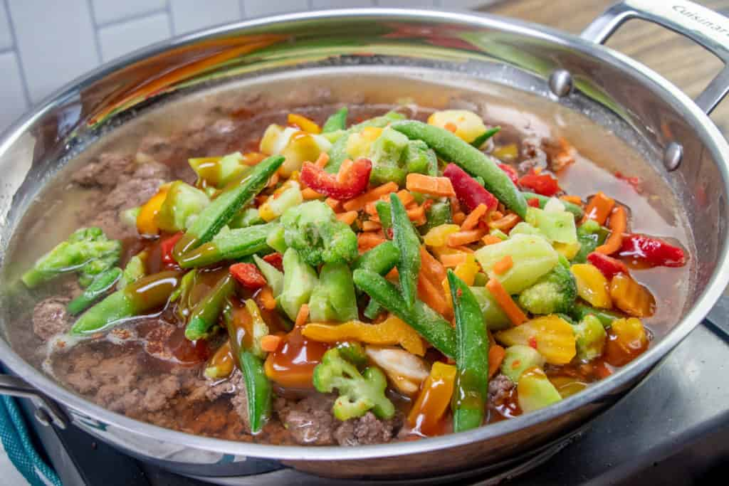 water, cooked ground beef, frozen stir fry vegetables and stir fry sauce in a large skillet