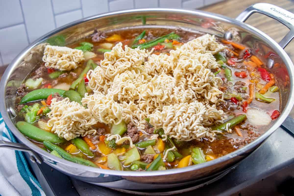 uncooked ramen noodles added to large stir fry skillet.