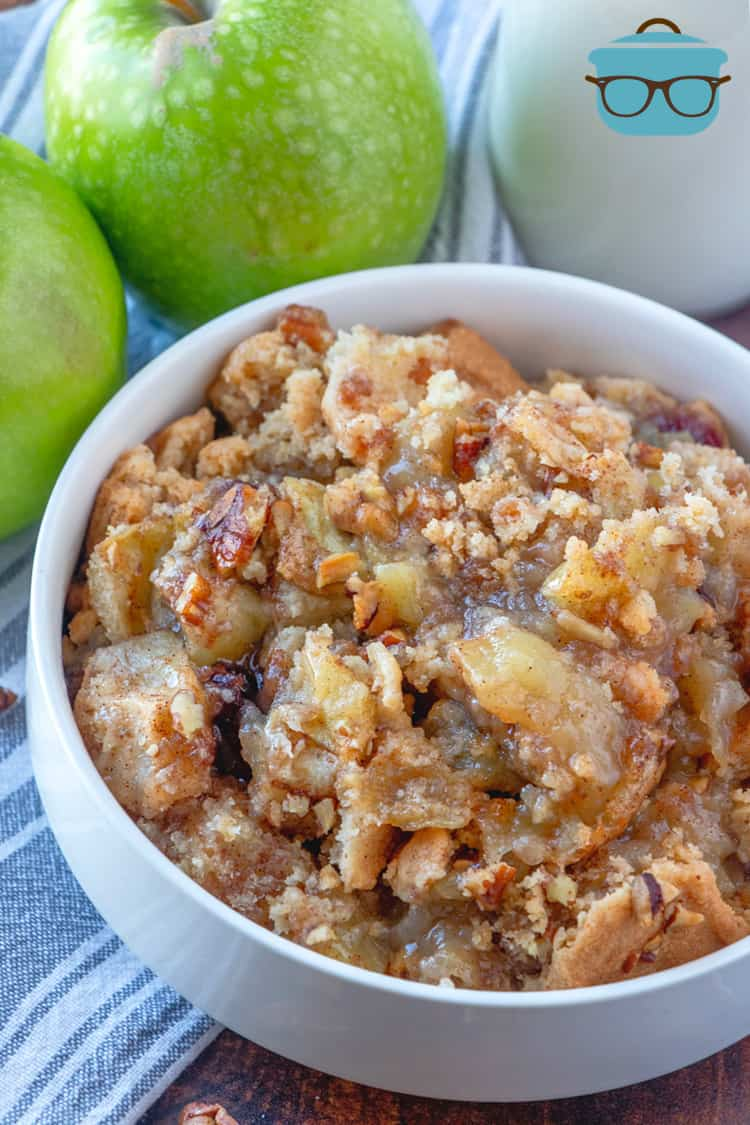 apple cobbler in a white bowl with two green apples and a glass of milk in the background.