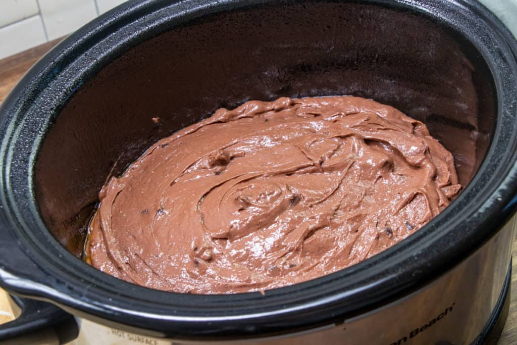 chocolate cake batter in the bottom of a small oval slow cooker