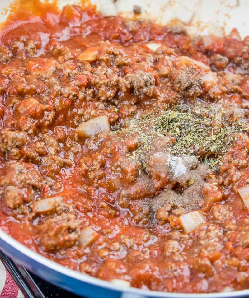 Italian seasoning added to ground beef, onion, garlic, sugar, tomato sauce and crushed tomatoes