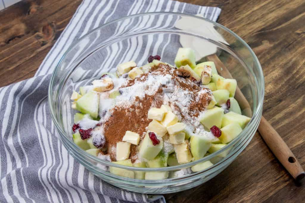 diced green apple, dried cranberries, sugar, flour, ground cinnamon, butter combined in a clear mixing bowl