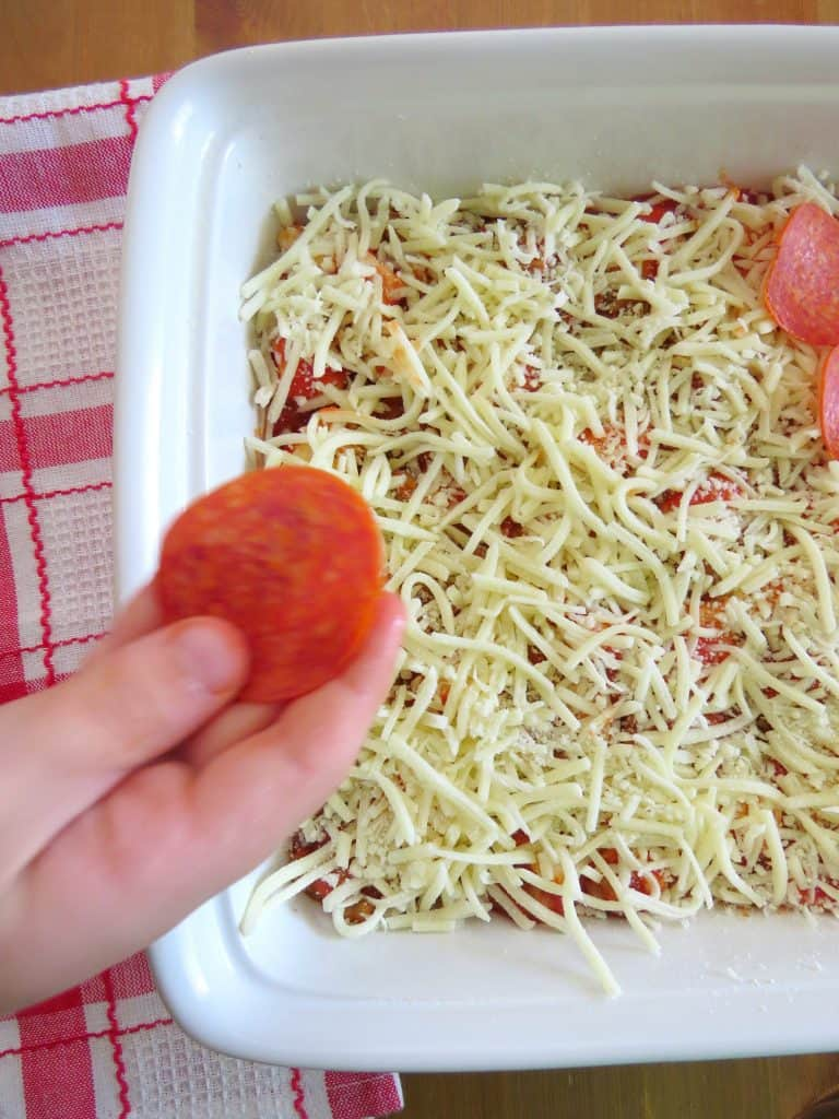 Alex adding pepperoni slices to bubble up pizza casserole