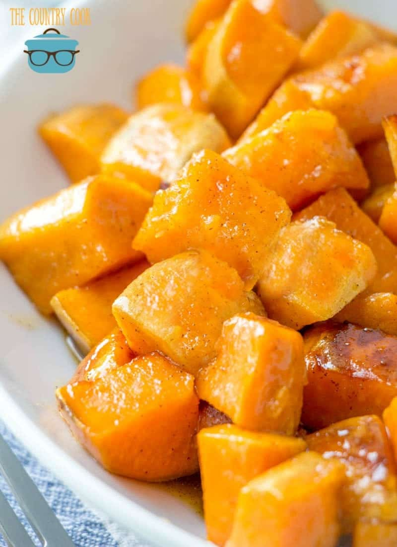 Honey glazed cinnamon sweet potatoes shown in a white bowl with a fork on the side.