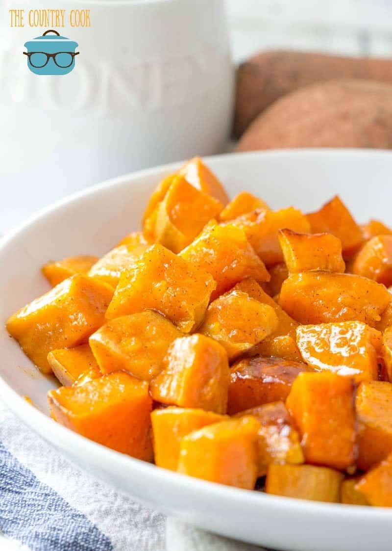 white shallow bowl full of honey glazed sweet potatoes.