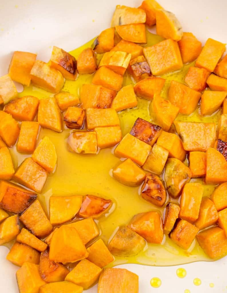 honey added to diced sweet potatoes in a large skillet