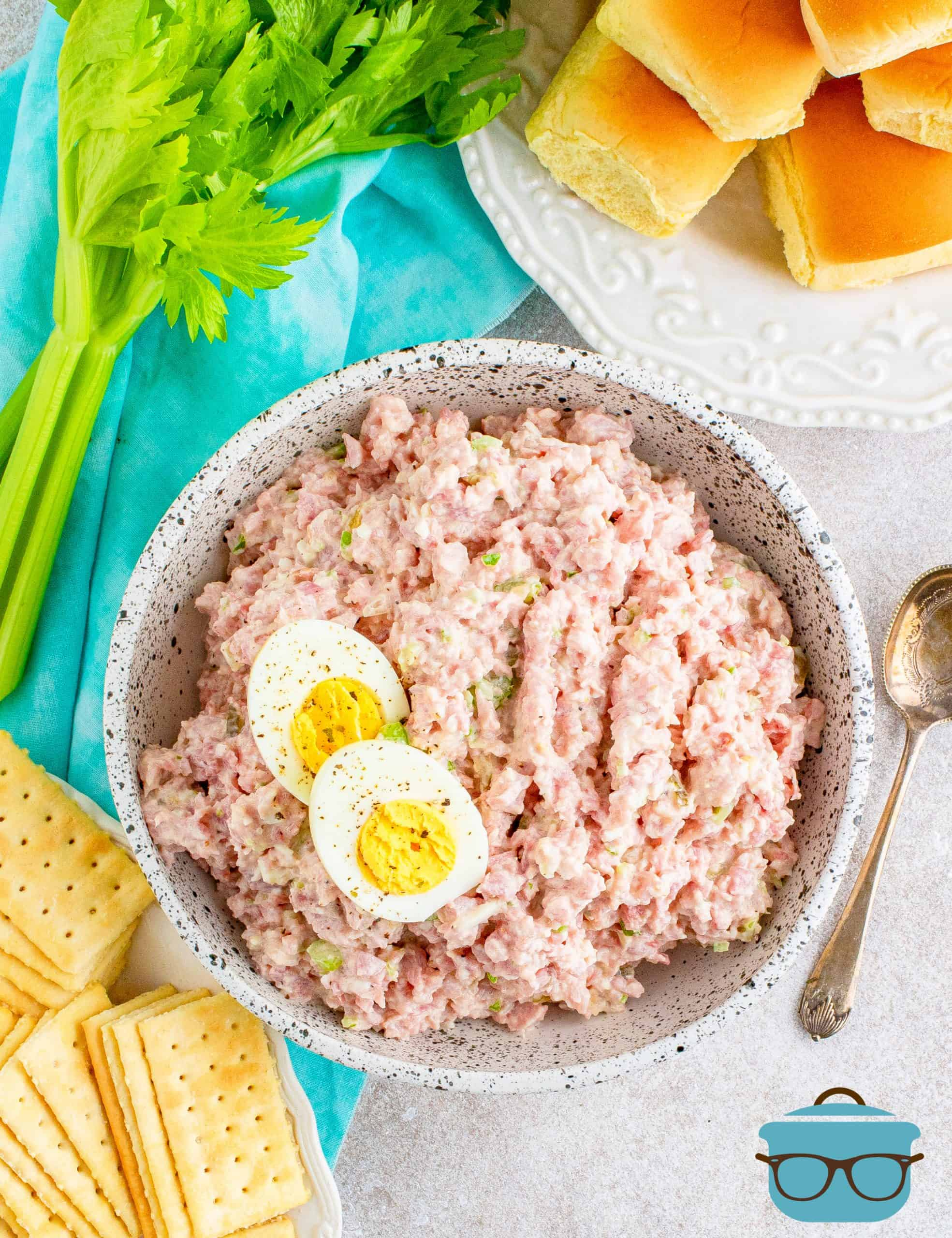 overhead shot of ham salad in a bowl with rolls and crackers off to the side