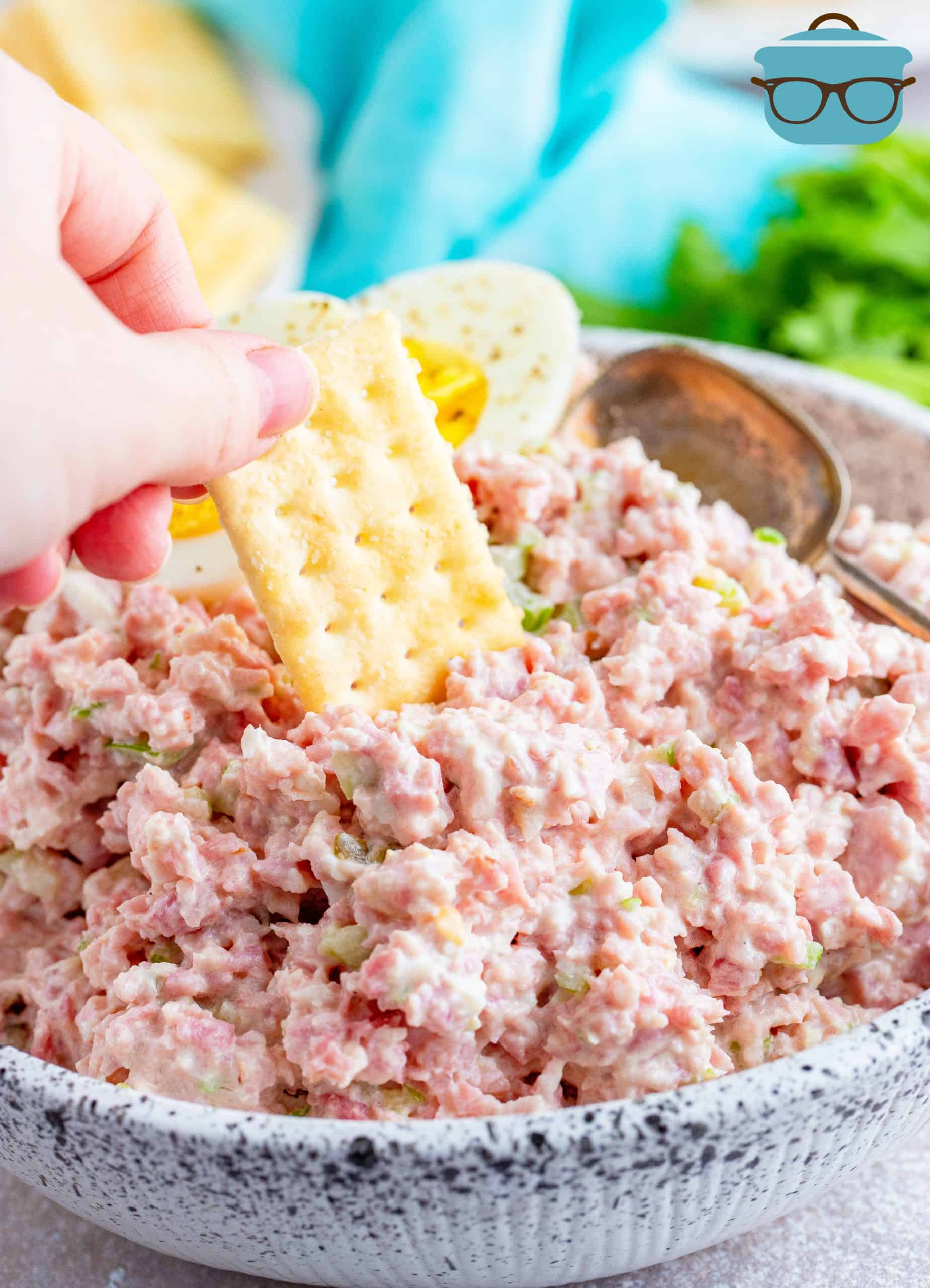 ham salad shown in a white speckled bowl with a hand dipping a club cracker into the ham salad