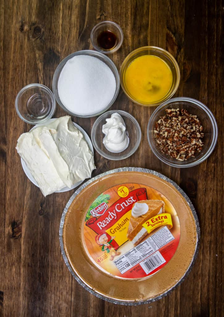 store-bought graham cracker crust (extra 2 servings size), cream cheese, sugar, sour cream, eggs, butter extract, vanilla extract, chopped pecans