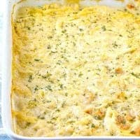 fully cooked chicken and dumplings casserole in a white baking dish topped wih chopped parsley