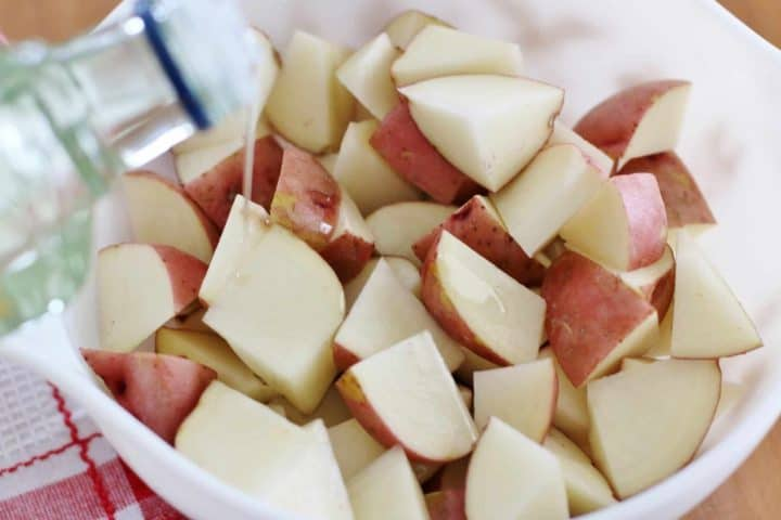 drizzling olive oil overdiced red potatoes in a bowl.
