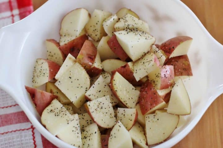 diced red potatoes shown with lemon pepper seasoning and salt on top.