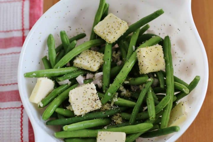 fresh green beans topped with pats of butter and seasoning in a white bowl.