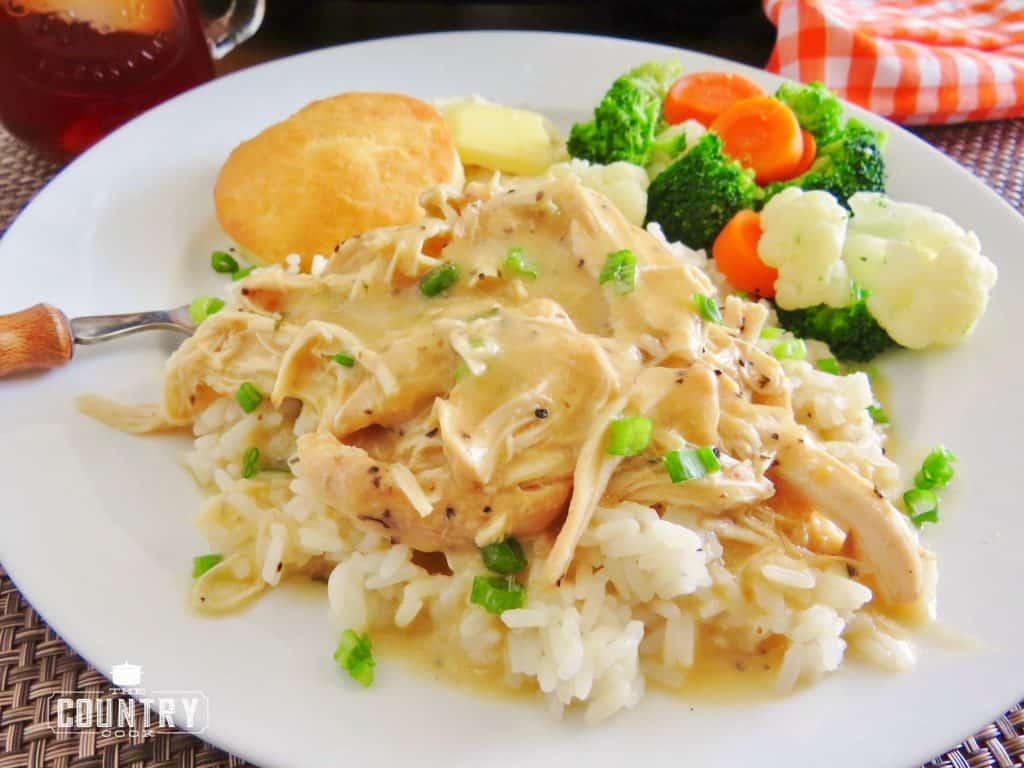 Crock Pot Chicken and Gravy poured over cooked white rice, served with biscuits and steamed vegetable medley on a white plate, wooden fork and sweet tea in a mason jar in the background