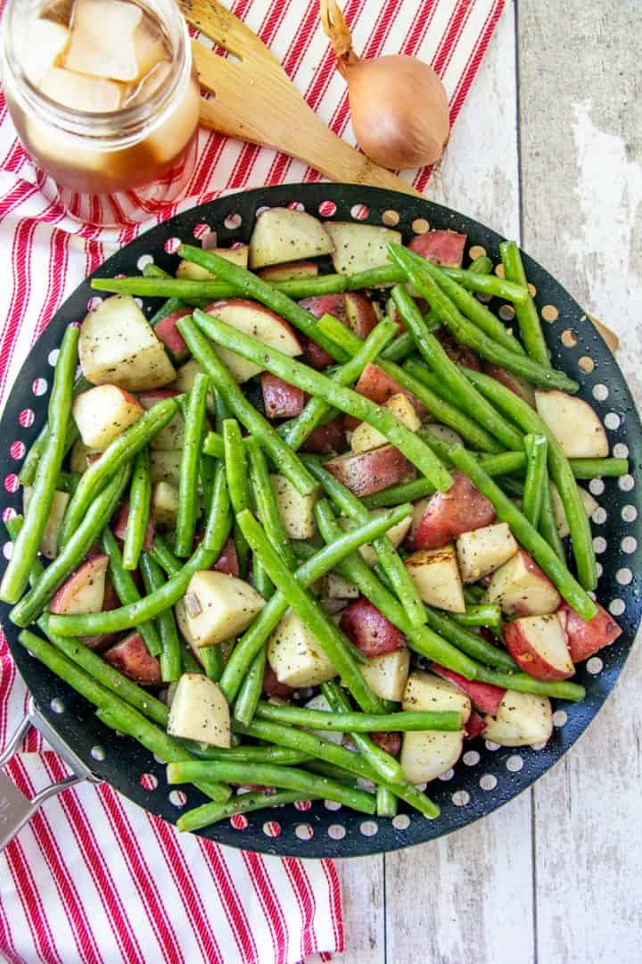 Diced potatoes and fresh green beans shown in a black grill pan with a glass of iced tea off to the side of the basket.