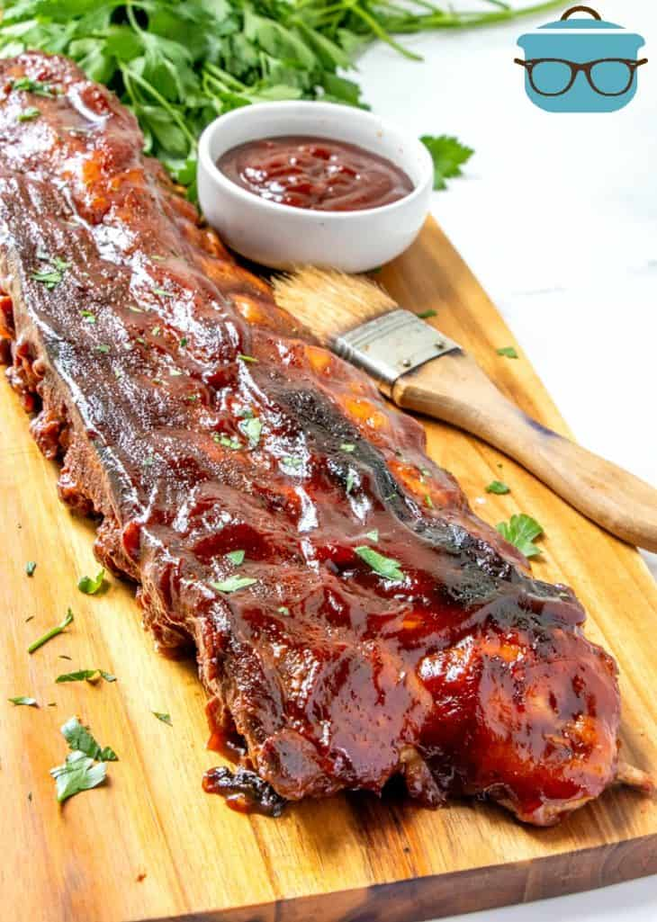 Allow Cooker Baby Back Ribs on a wooden platter covered in barbecue sauce