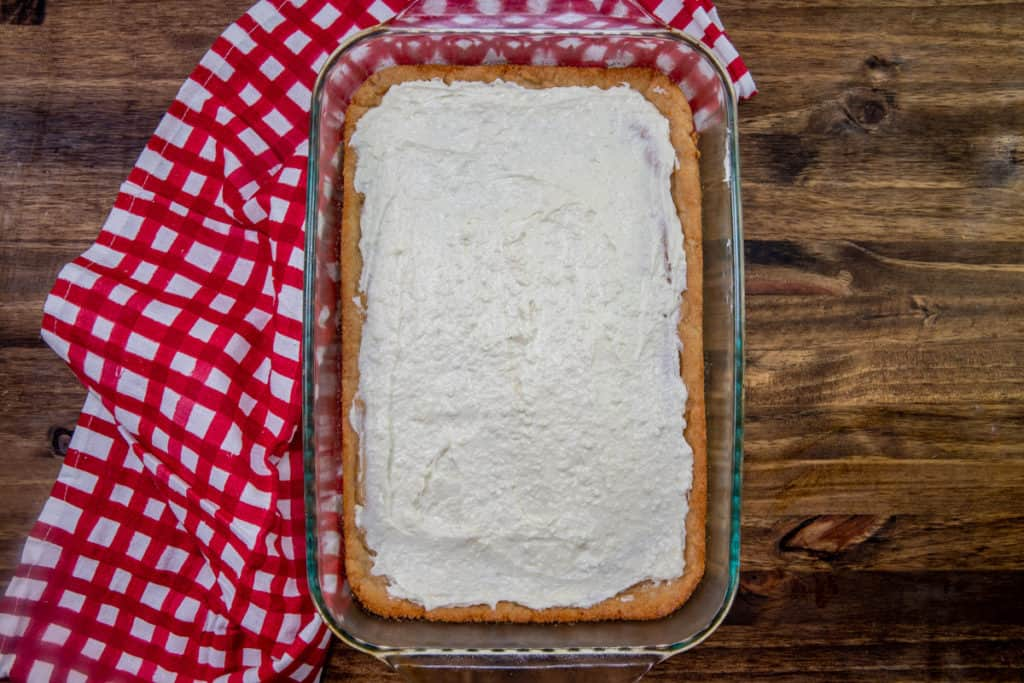white chocolate cream cheese mixture spread onto cooked cookie dough crust in a glass baking dish