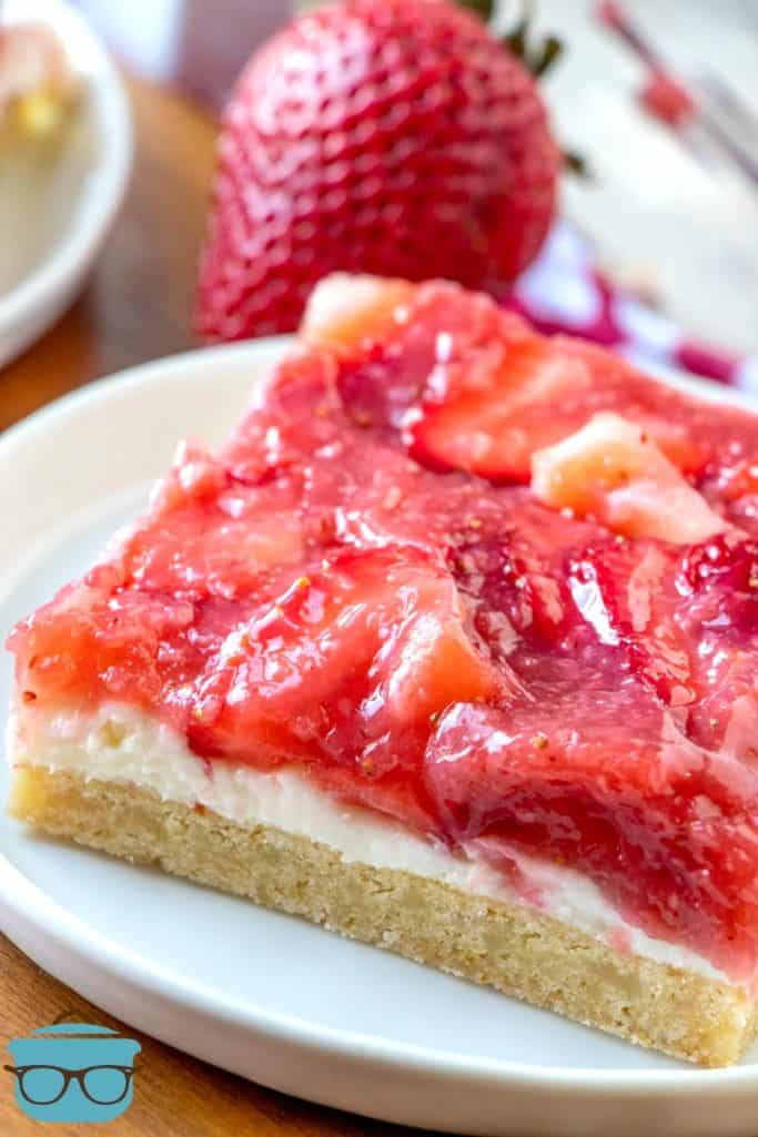 slice of Strawberries and Cream Cookie Bars on a white plate with a strawberry in the background