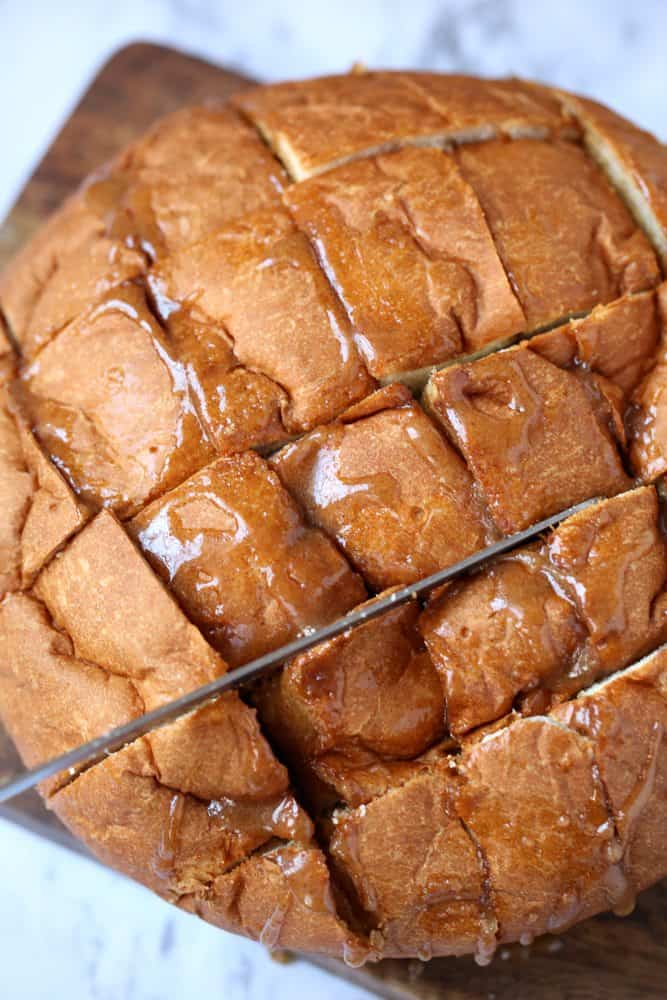 slicing sweet round bread with brown sugar, butter glaze
