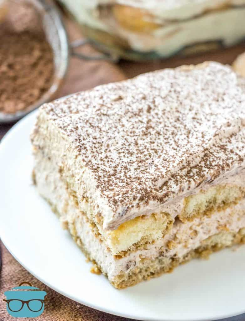 The Easiest Tiramisu recipe, slice on a white plate and dusted with cocoa powder