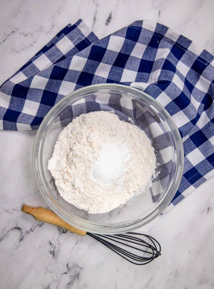 flour, baking soda and salt shown in a clear mixing bowl with a whisk set to the side of the bowl