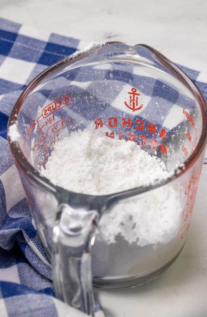 powdered sugar and milk in a glass measuring cup