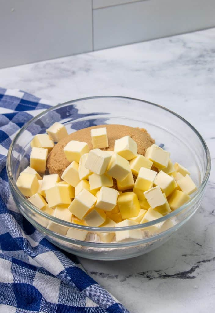 cubed butter and brown sugar shown in a clear glass bowl