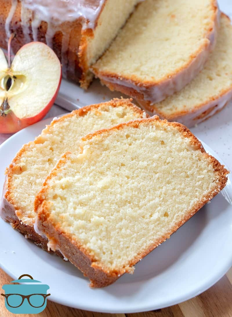 Apple Cider Pound Cake slices on a white plate with apple in the background.