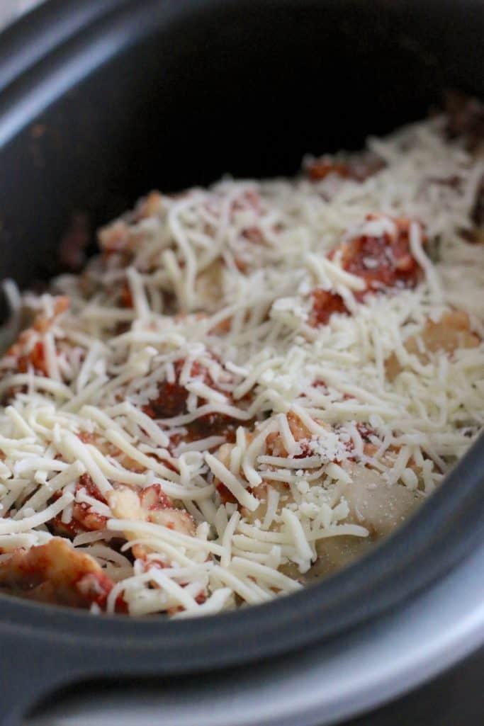 cooked ravioli, marinara sauce and shredded mozzarella cheese in an oval Ninja slow cooker