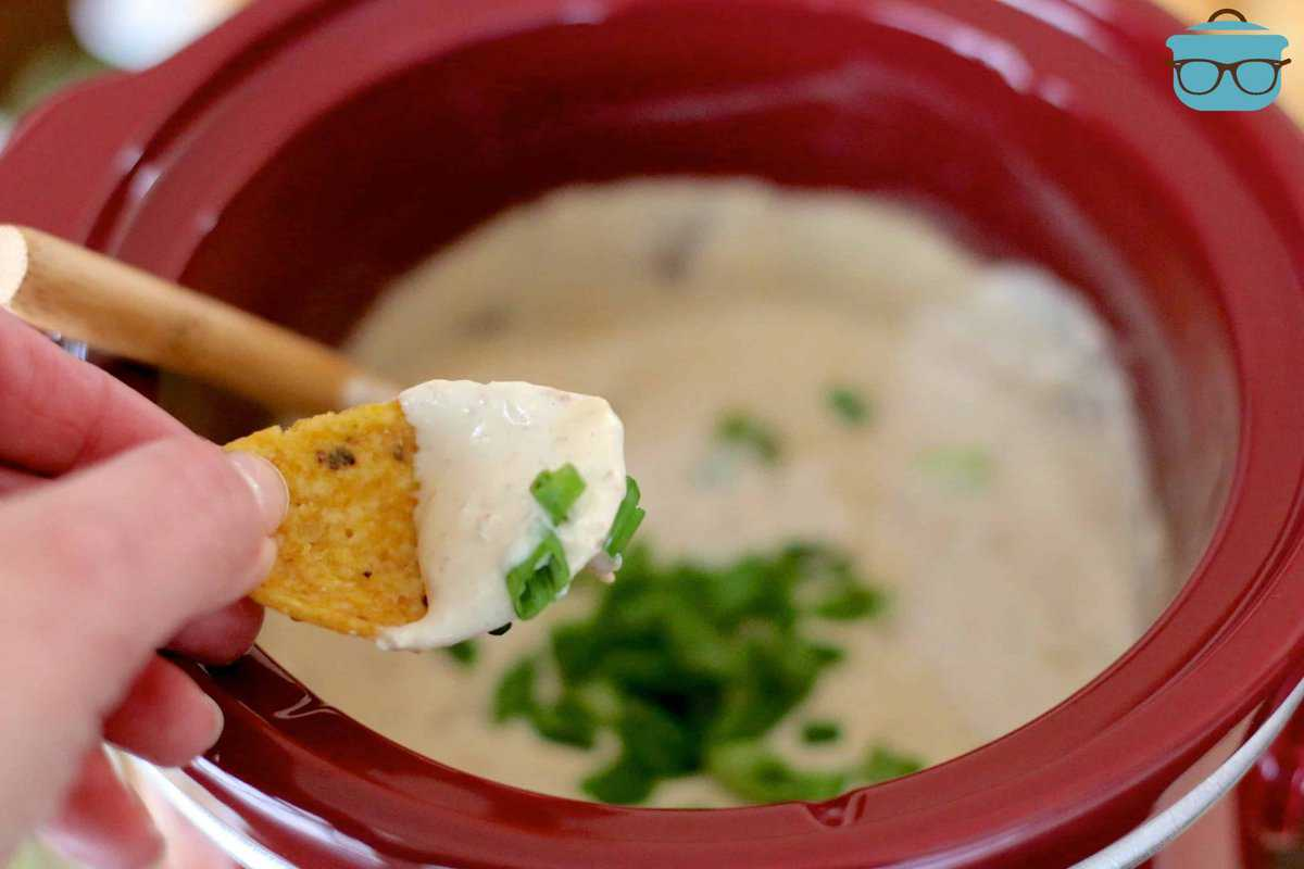 Dipping a Frito chip into warm french onion dip