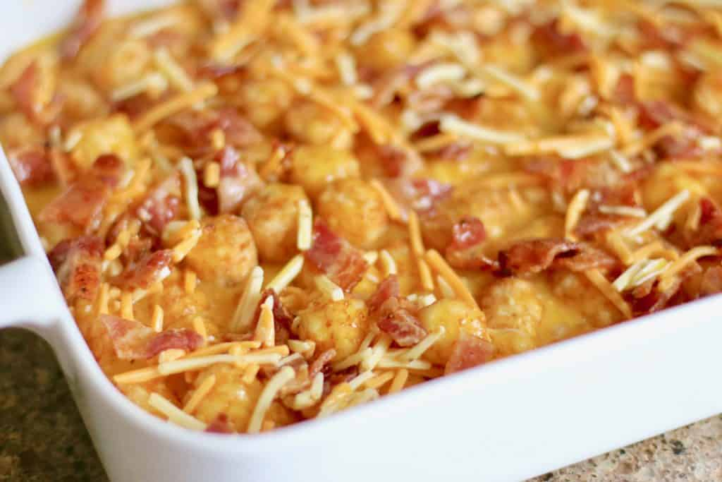 tater tots topped with whisked eggs, shredded cheddar cheese and bacon