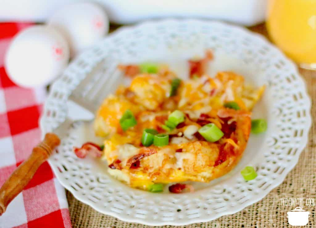 Tater Tot Breakfast casserole with eggs and bacon on a small white lace-patterned serving plate