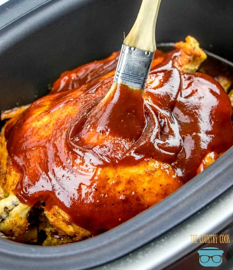 spreading Sweet Baby Ray's BBQ sauce on top of slow cooker bbq chicken
