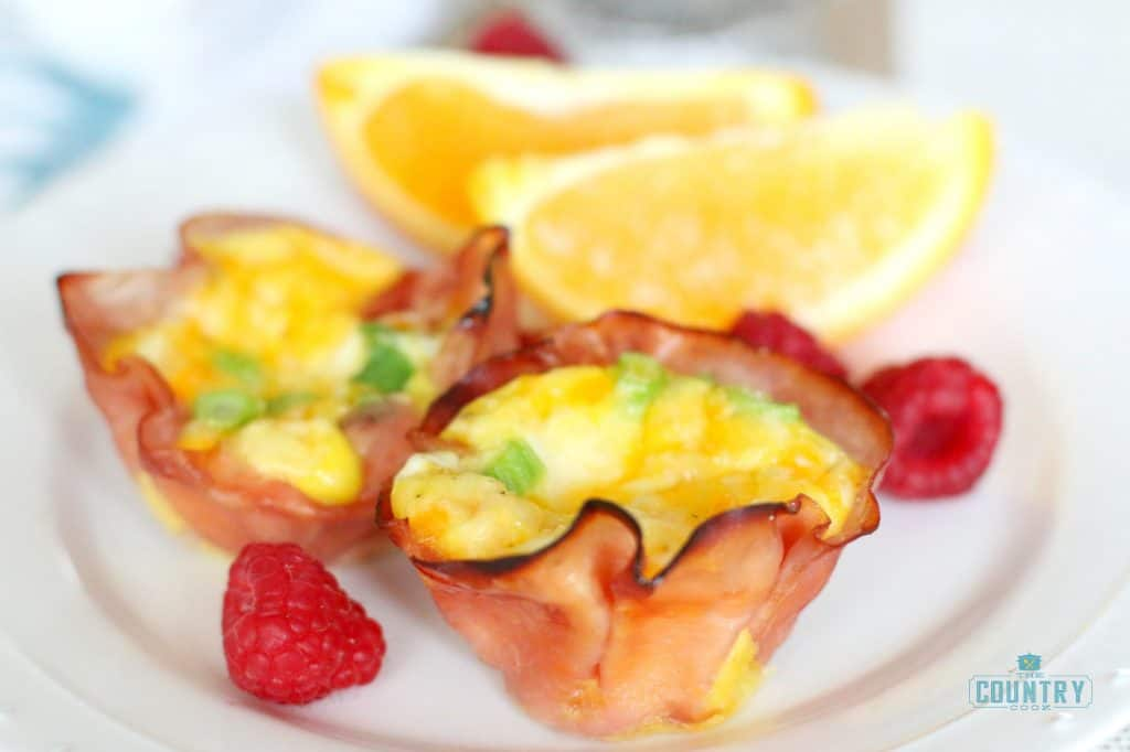 Ham and scrambled eggs on a plate with fruit
