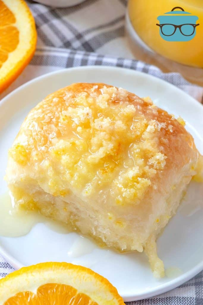 freshly baked glazed orange roll on a plate with fresh oranges
