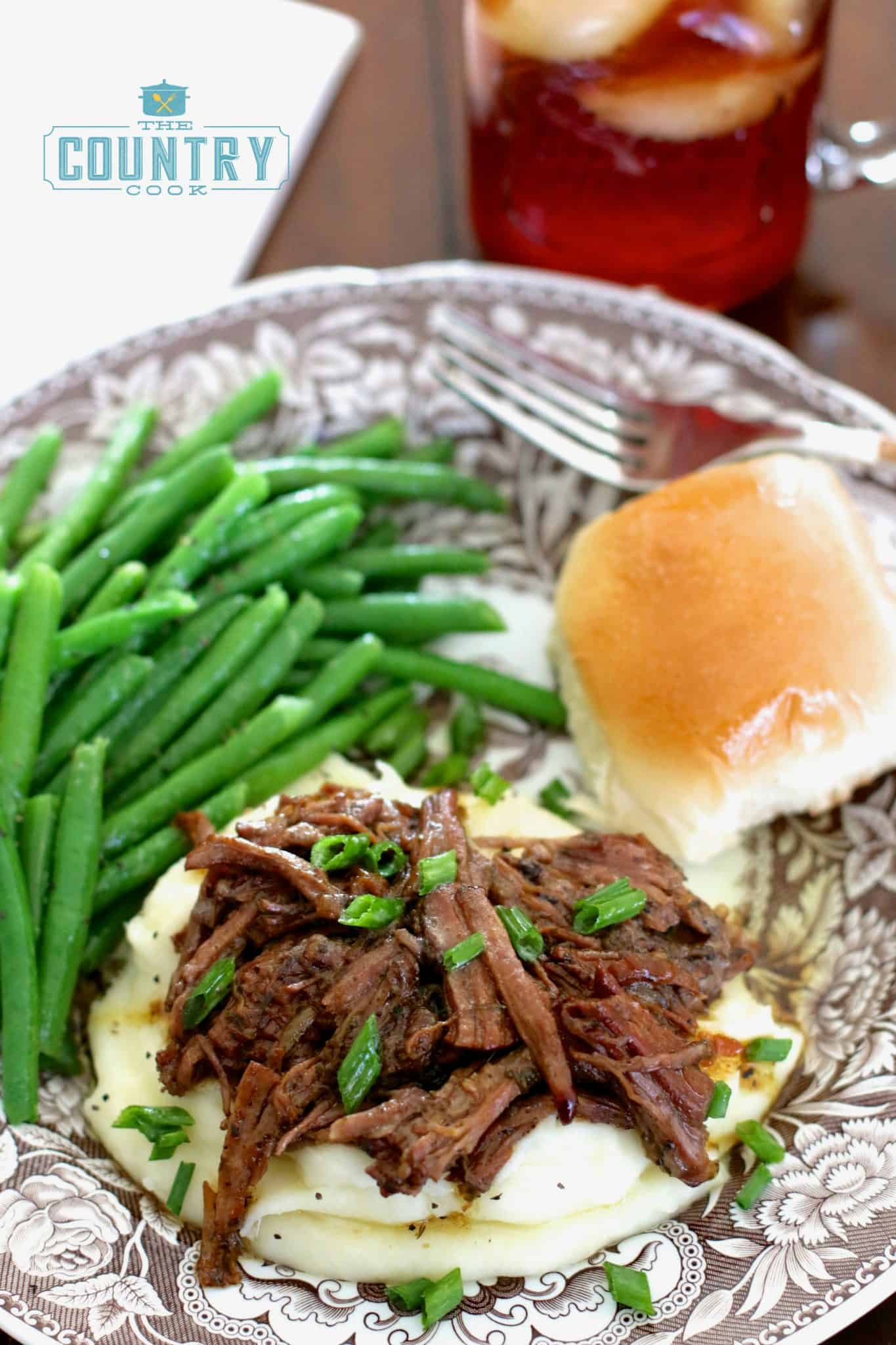 serving of shredded pot roast on mashed potatoes with fresh green beans and a roll on a plate