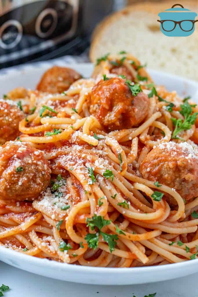 close up of Spaghetti and Meatballs in a white bowl with slices of bread in the background
