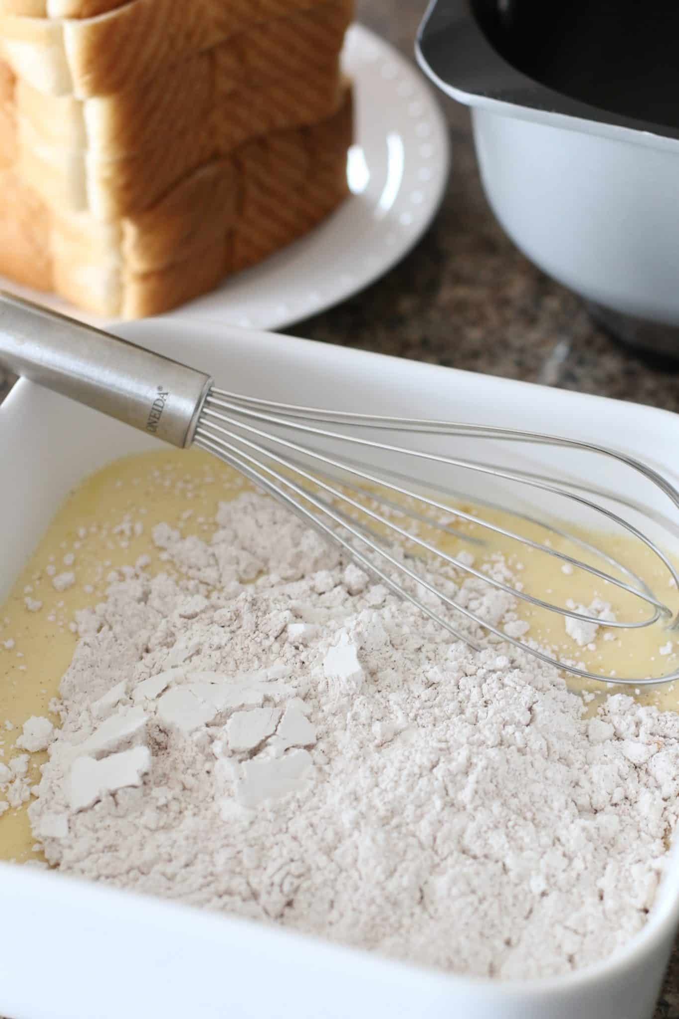 whisking flour and eggs together in a white square dish.