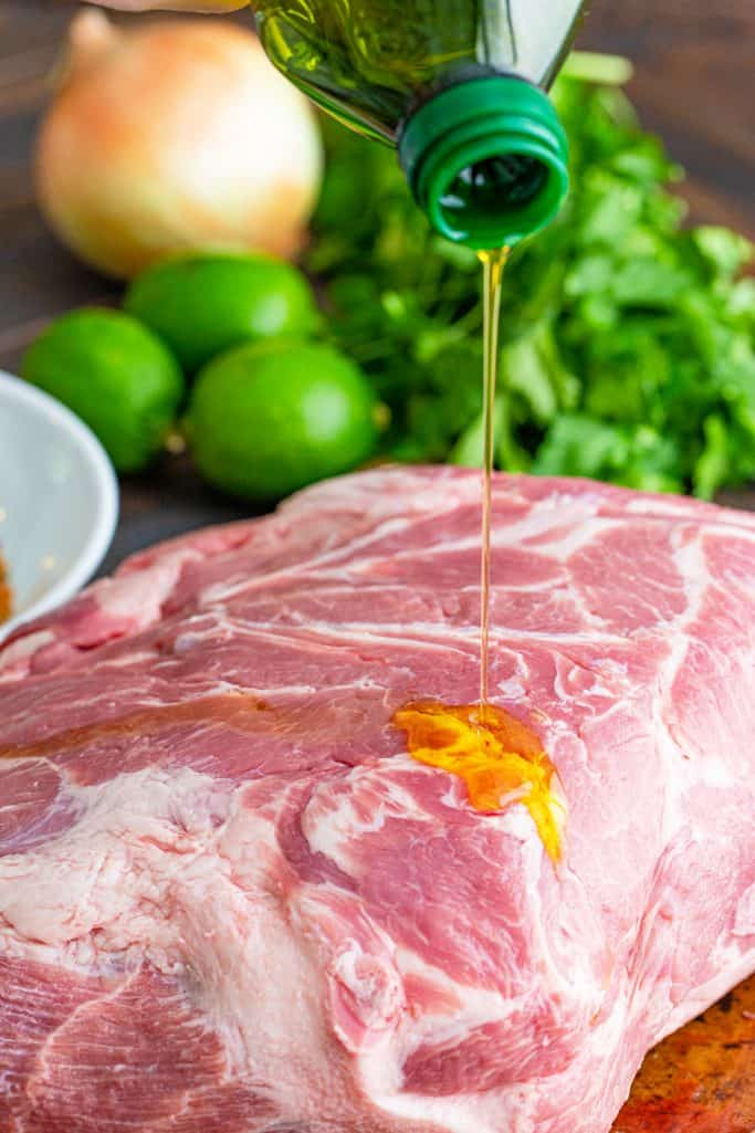 pouring olive oil on a pork roast