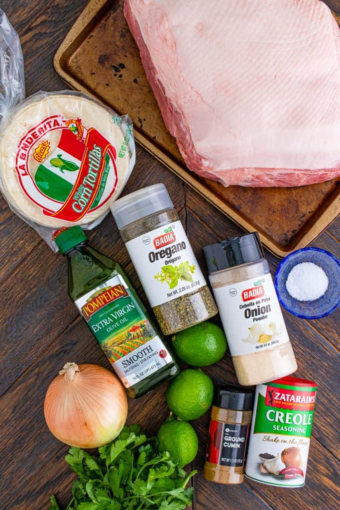 Ingredients for slow cooker carnitas: Boston butt (pork shoulder roast), corn tortillas, creole seasoning, kosher salt, cumin, oregano, onion powder, limes