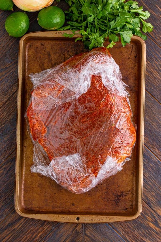 seasoned pork roast wrapped in plastic wrap