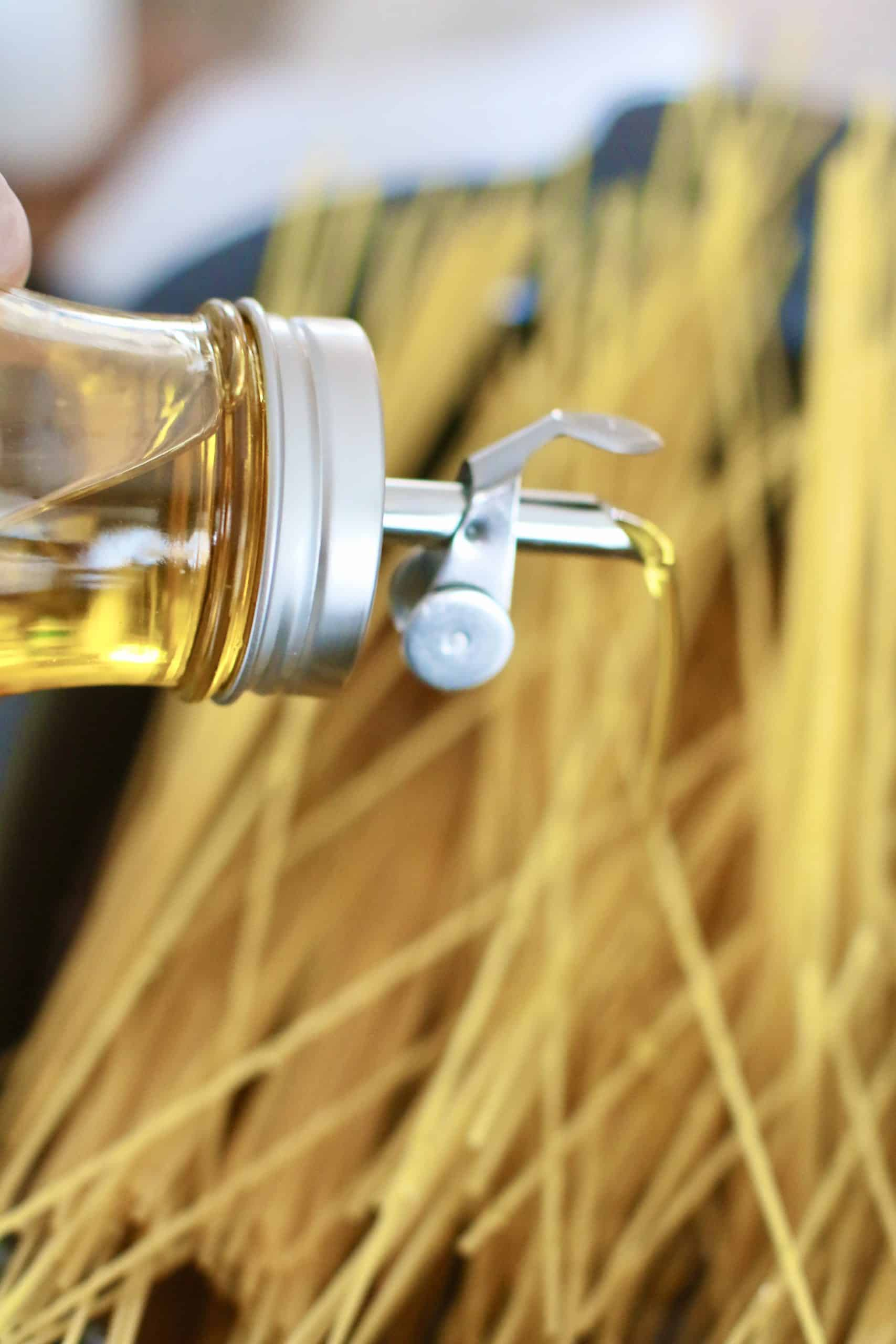 sizzling olive oil on top of spaghetti noodles