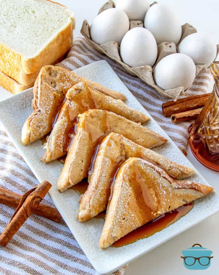 5 triangle slices of fluffy French toast lined up on a white tray with eggs in the background