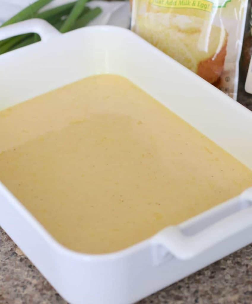 Cornbread batter in a square white baking dish